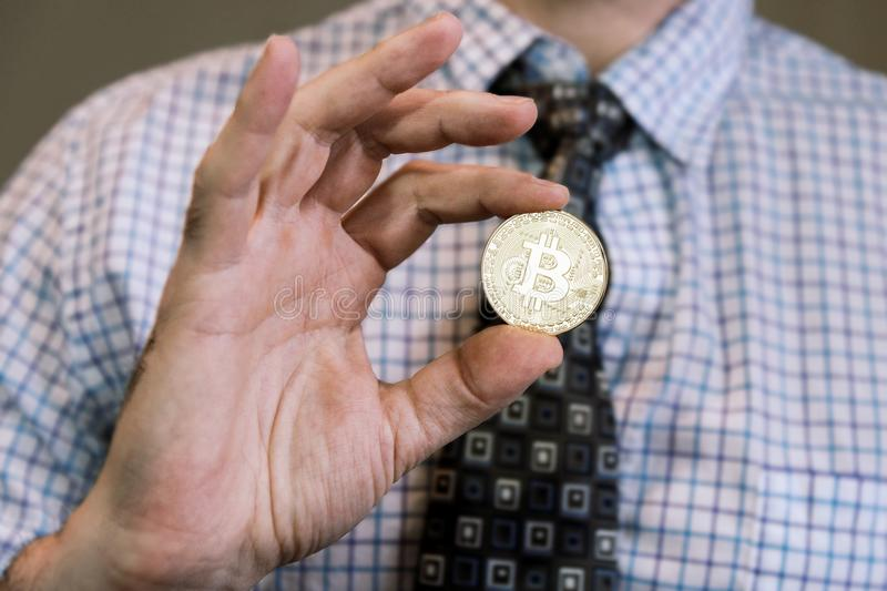 Minted gold Bitcoin token in hand stock photos