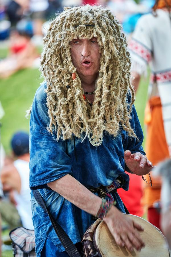 Caucasian male hippie percussionist wearing a dreadlock wig playing rhythm with his djembe drum bongo. Montreal, Canada - June, 2018. Caucasian male hippie royalty free stock photos