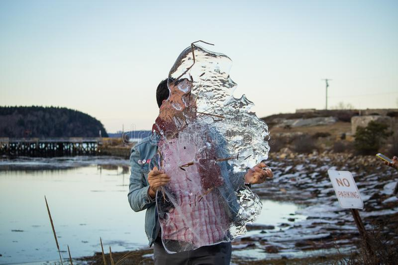 A caucasian male holding a giganctic piece of ice in his hands with a lake in the background royalty free stock photo