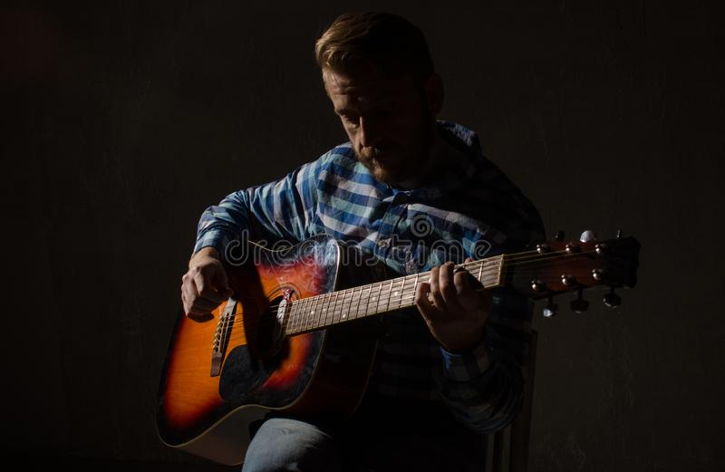 Caucasian male jazz musician playing guitar on stage,. Focus on hand stock image