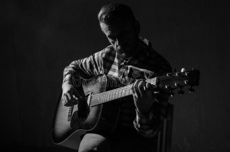 Caucasian male musician playing guitar on stage, focus on hand. black and white.  stock images