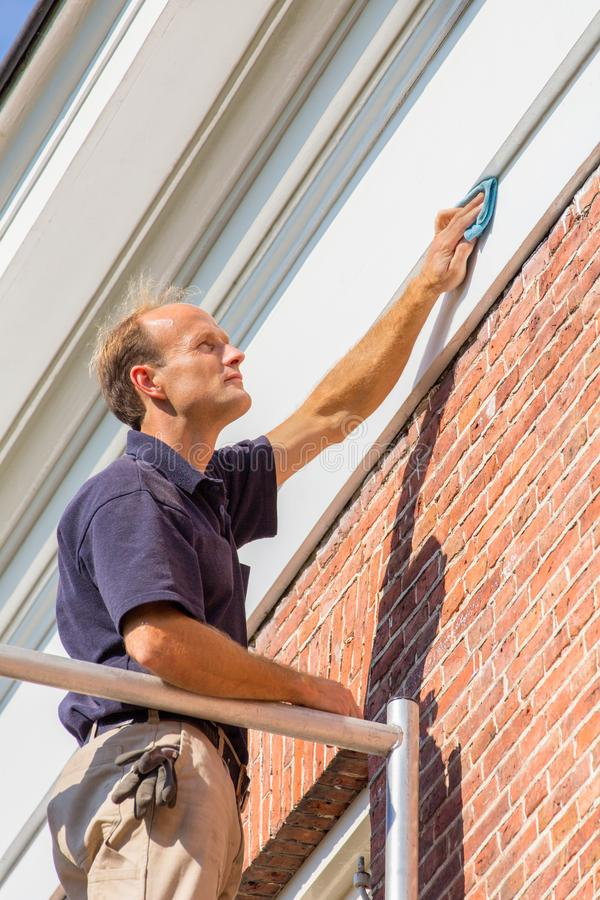 Caucasian male painter cleaning roof molding with cloth royalty free stock photo