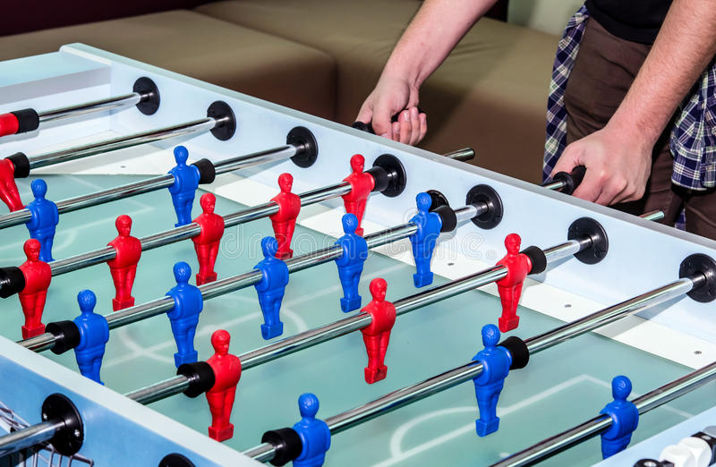 Caucasian male playing table soccer game stock photos