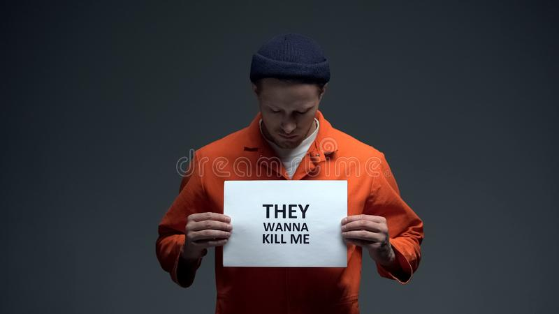 Caucasian male prisoner holding They wanna kill me sign, calling for help stock photography