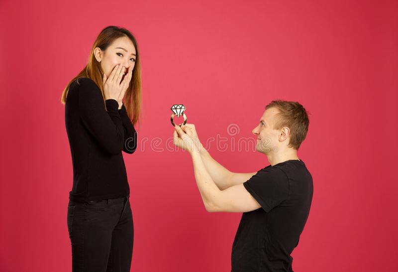 Caucasian male proposing to his asian girlfriend with an oversized engagement ring stock images