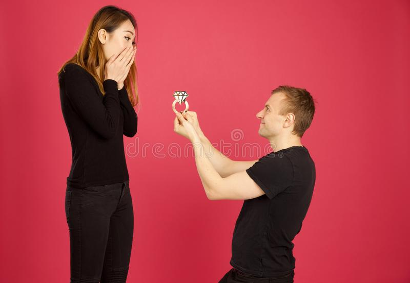 Caucasian male proposing to his asian girlfriend with an oversized engagement ring stock photo
