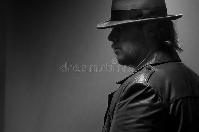 Caucasian Male in vintage trench coat and fedora. Black and white gaze stock photo
