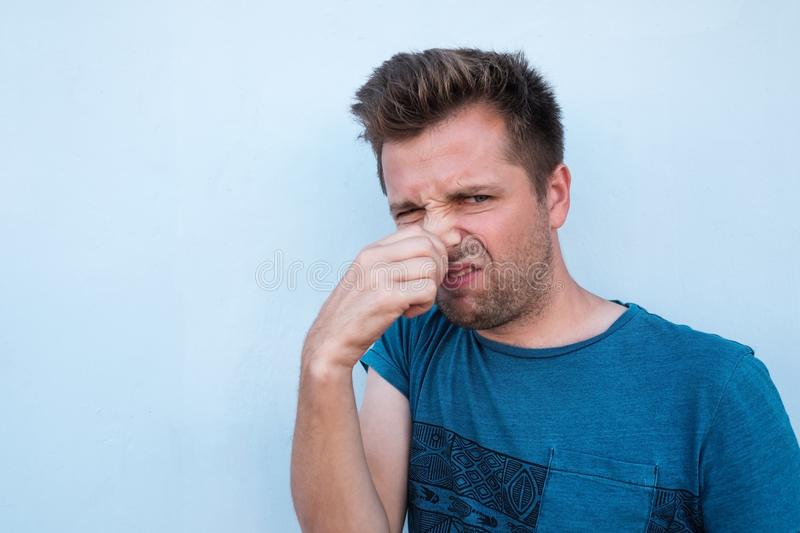 Caucasian man in blue shirt closing his nose because of bad smell. stock images