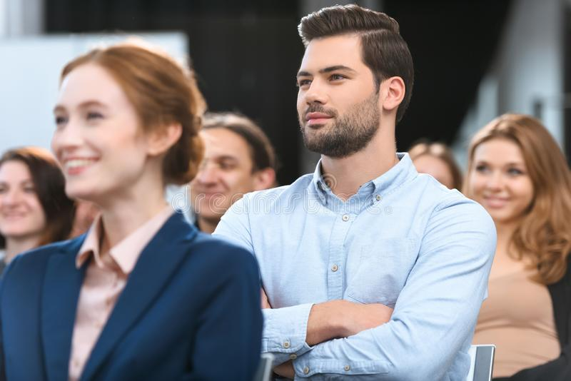 Caucasian man in blue shirt looking away while sitting stock photography