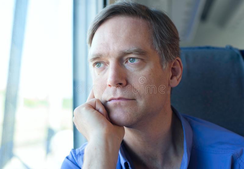 Caucasian man in blue shirt sitting on train at daytime royalty free stock photo