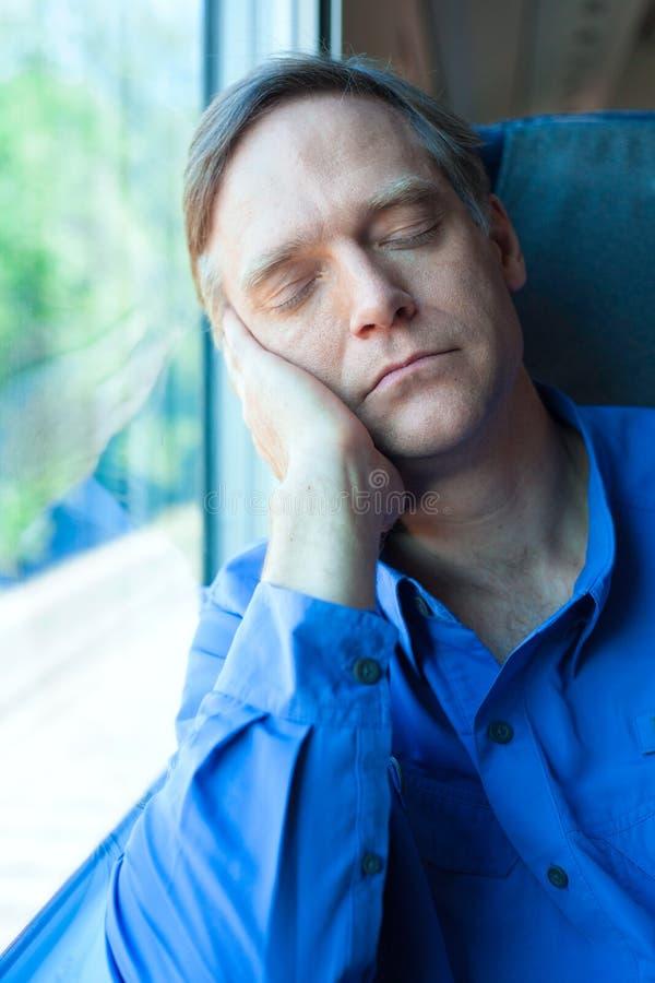 Caucasian man in blue shirt sleeping against train window stock images