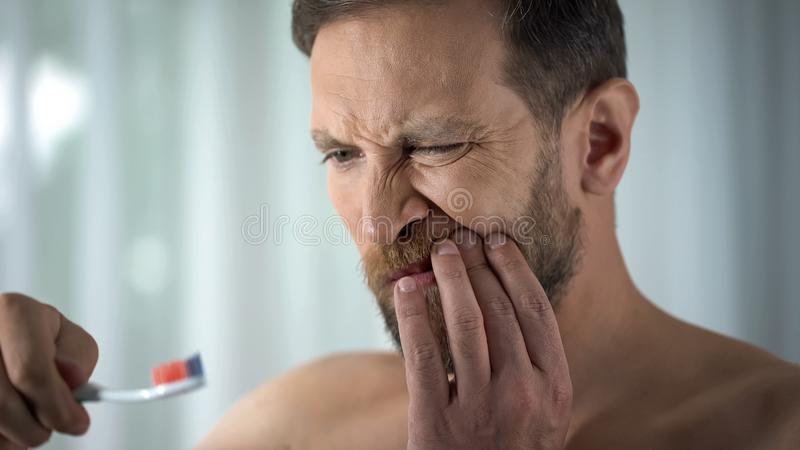 Caucasian man brushing teeth and seeing blood on toothbrush, dental care, ache. Stock photo stock photo