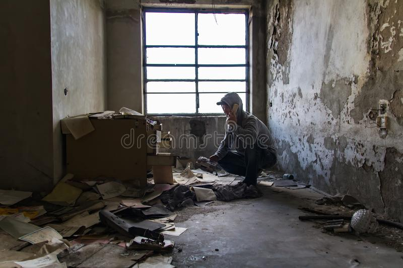 Caucasian man in cap and hood phone with broken phone in abandoned building. Hacker, racketeer, terrorist concept royalty free stock image