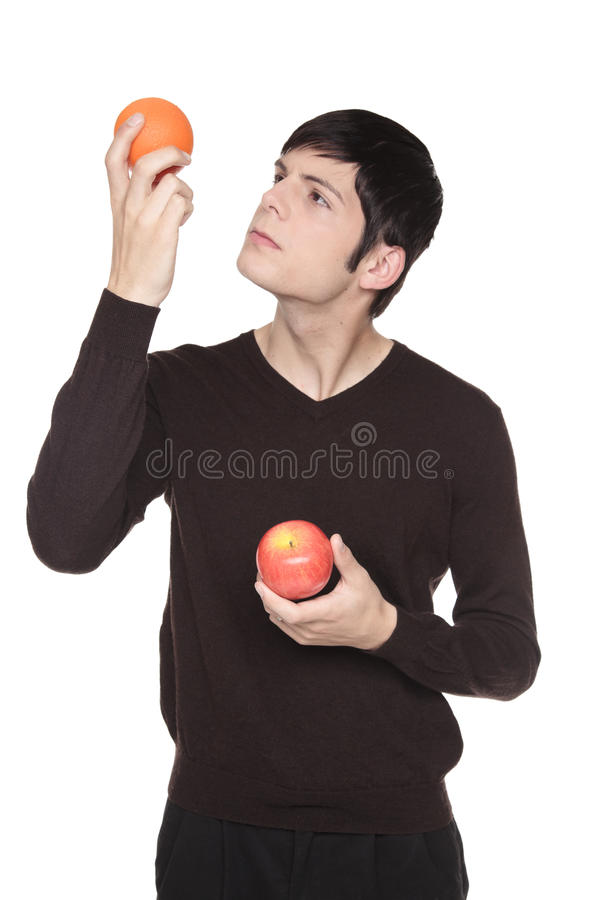 Caucasian man comparing apple to orange stock photography