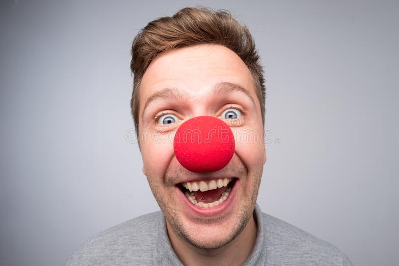 Caucasian man with crazy look wearing a clown nose stock images