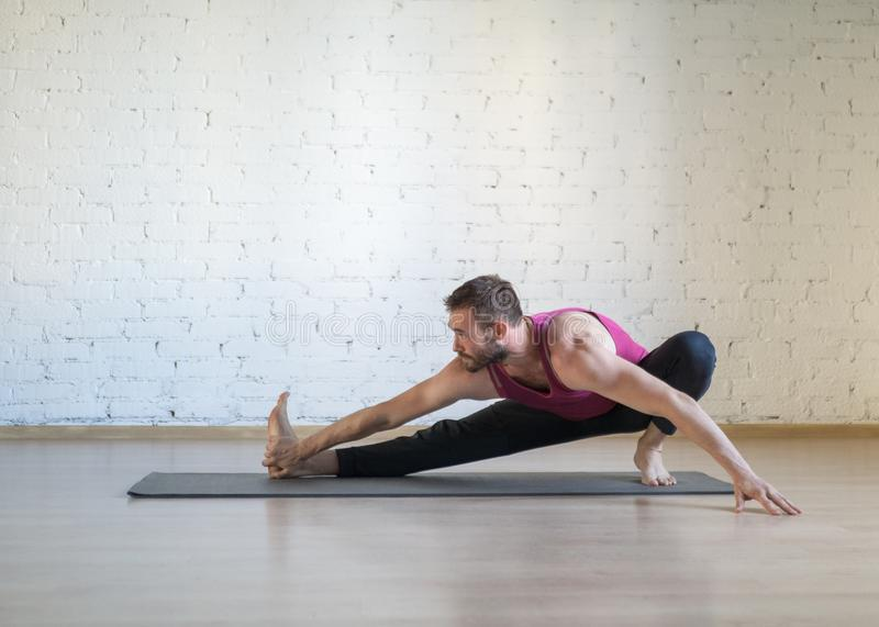 Caucasian man doing stretching, warm-up, yoga on grey mat in fitness studio, loft style, selective focus. royalty free stock photos