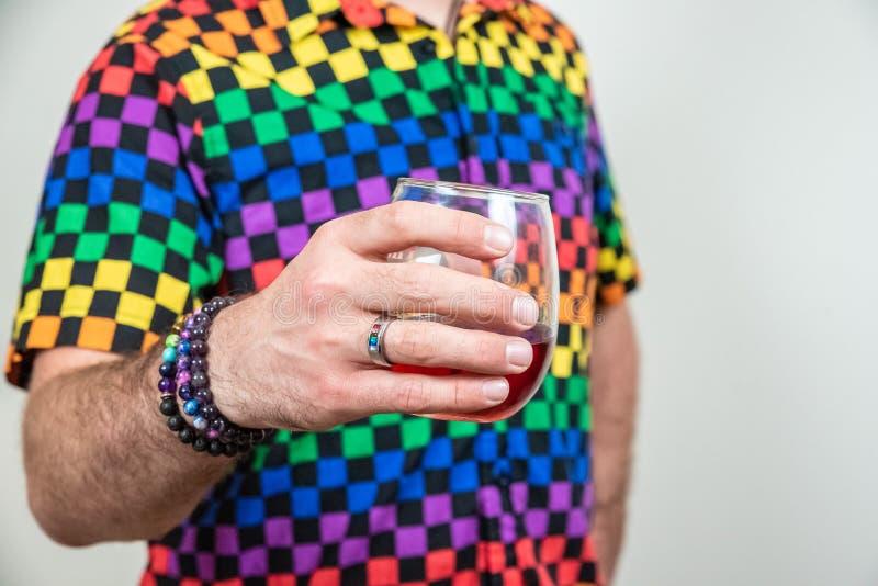 Caucasian man för färgrik lgbt som rymmer stemless exponeringsglas för vin, vit bakgrund arkivbilder
