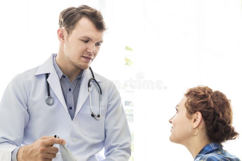 Caucasian man för medicinska professionell som uppmuntrar och talar med spänningspatienten för ung kvinna royaltyfria bilder