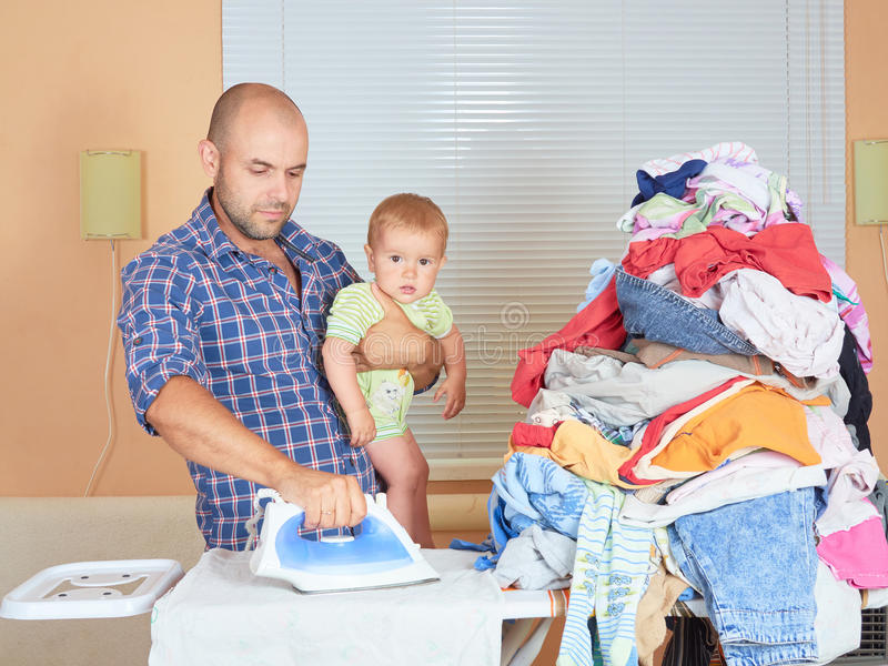 Caucasian man father and son in his hands, ironed clothes in the stock photography