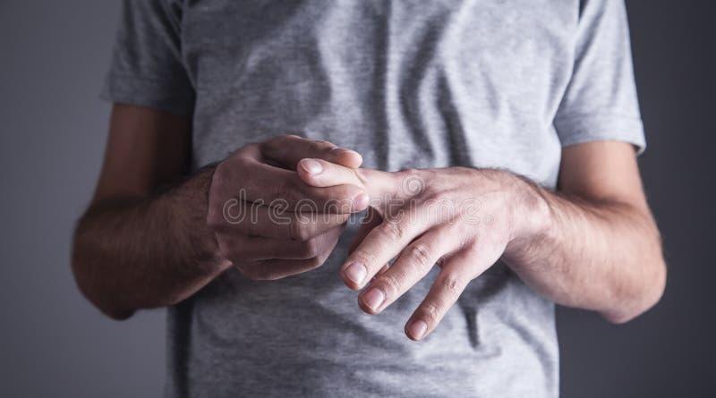 Caucasian man with finger ache. Arthritis, wrist pain stock images