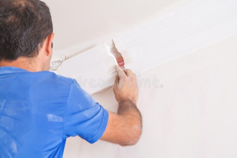 Caucasian man fixes ceiling skirting. Renovation stock photo