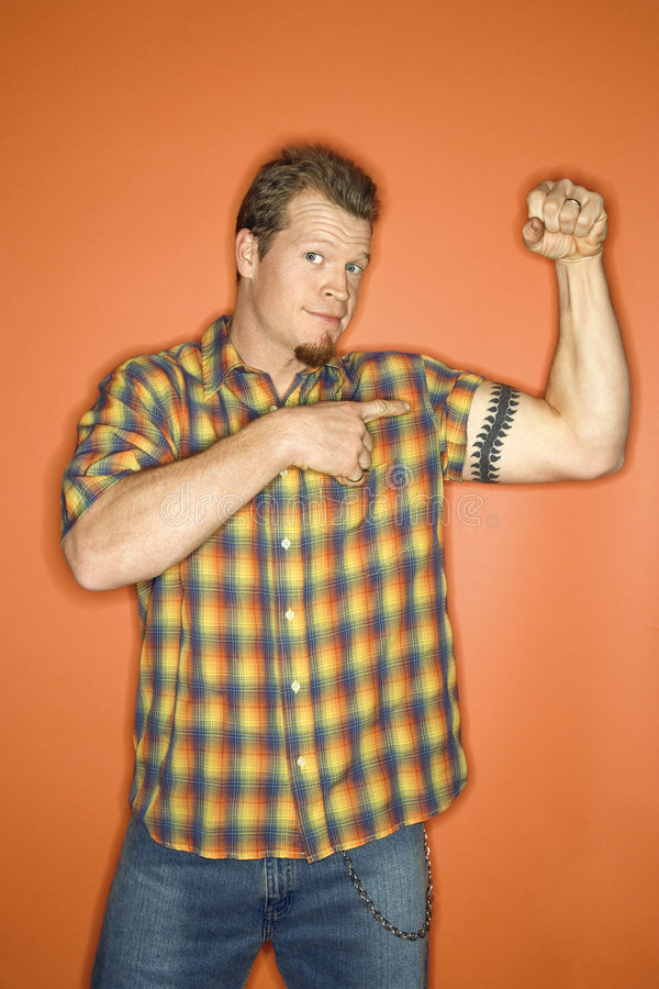 Caucasian man flexing his arm muscle. Portrait of adult Caucasian man on orange background flexing and showing off his arm muscle stock photography