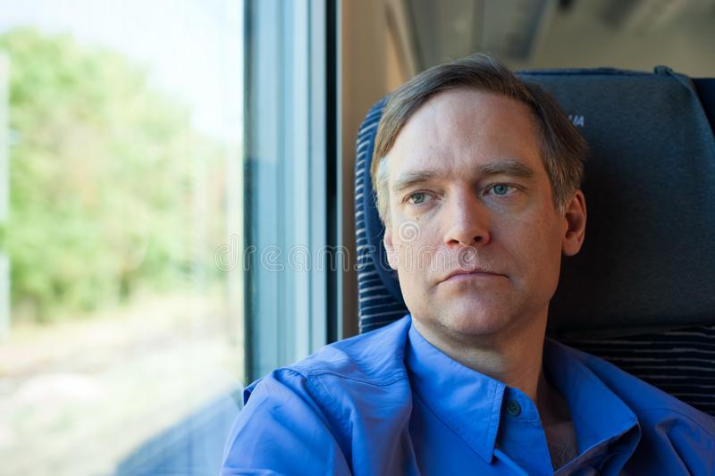 Caucasian man in forties sitting on train, commuting stock photo