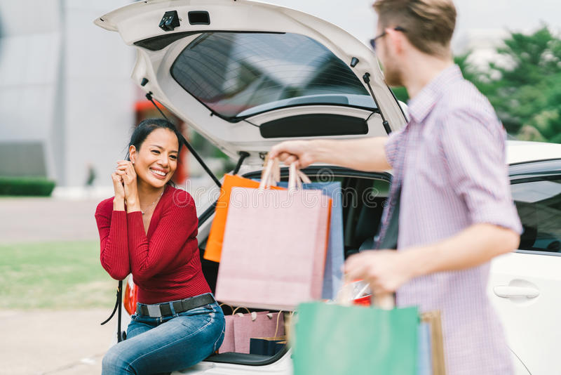 Caucasian man gives shopping bags to Asian woman sitting on car. Shopaholic, love, multiethnic couple, or casual lifestyle concept royalty free stock image