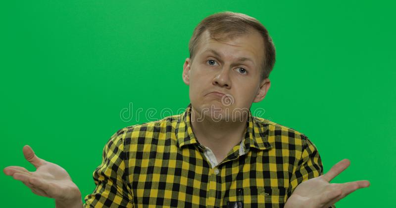 Caucasian man in glasses, doing gesture with hands like I don`t know or whatever. On the chroma key background. Green screen royalty free stock photography