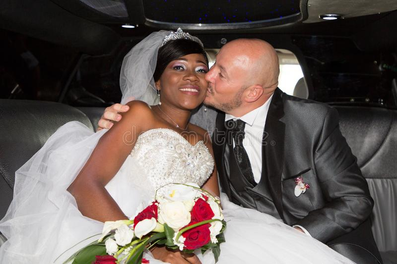 Caucasian man groom kissing her charming wife bride black african in luxury wedding car. Happy caucasian men groom kissing her charming wife bride black african royalty free stock photography