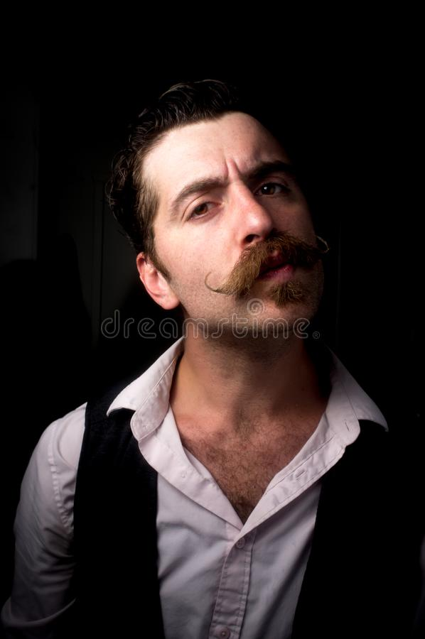 Caucasian Man Handlebar Mustache. Caucasian hipster man with large handlebar mustache wearing a dress shirt and suit vest royalty free stock image