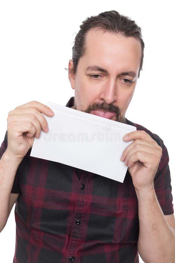 Caucasian man holding and licking a white envelope. Isolated on white stock image