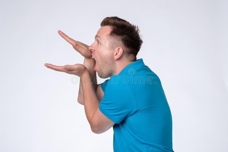 Caucasian man i den blåa skjortan som gör blablatecknet med hans hand arkivfoto