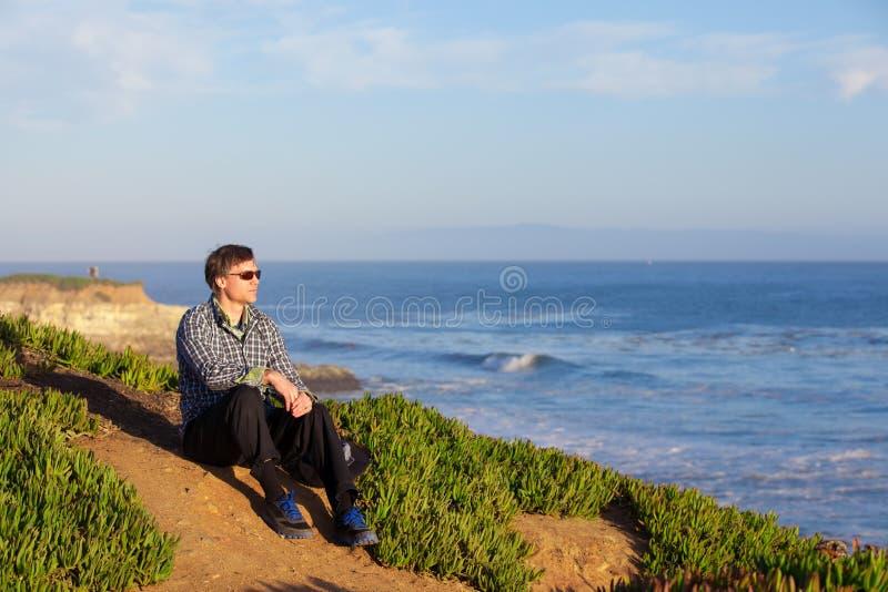 Caucasian man i tidigt femtiotal som sitter längs havkust royaltyfria bilder