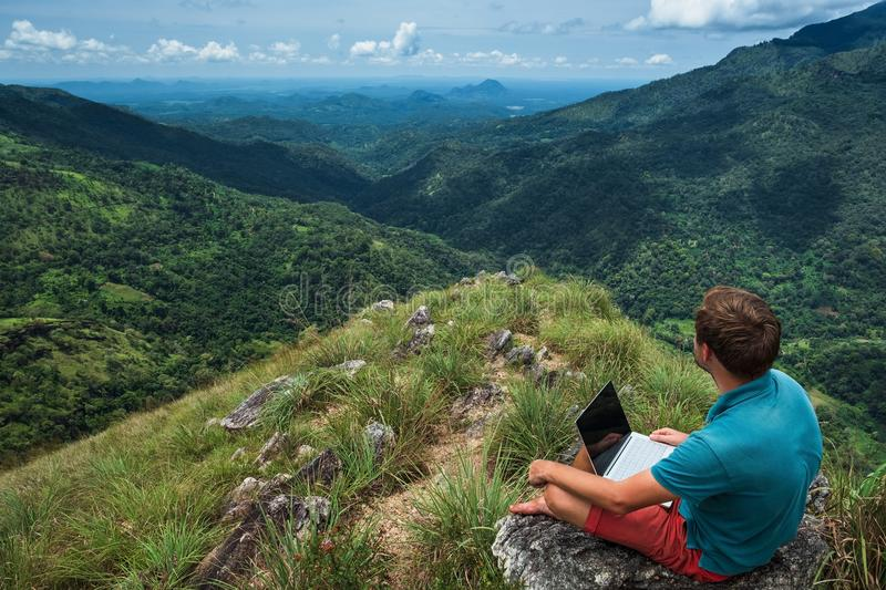 Caucasian man with laptop sitting on the edge of ella mountain with stunning views of the valley in Sri Lanka. royalty free stock image