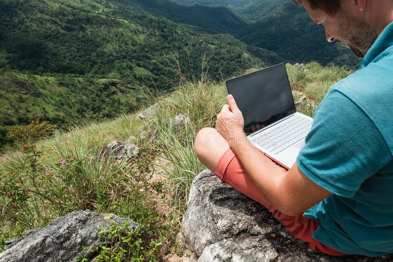 Caucasian man with laptop sitting on the edge of ella mountain with stunning views of the valley in Sri Lanka. royalty free stock photo