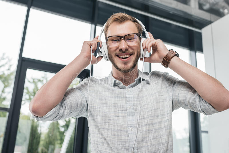 Caucasian man laughing and using headphones while looking at camera stock images
