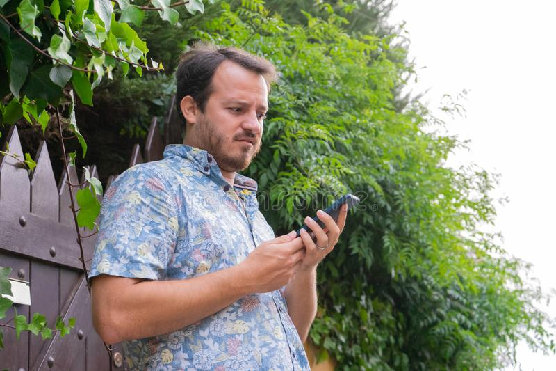 Caucasian man looking smart phone with expression of wonder and confused, reading an email. Serious man waiting, received a. Notification and shock, talking stock photography