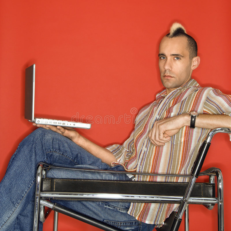 Caucasian man with mohawk with laptop. Caucasian man with mohawk holding laptop against red background stock photography