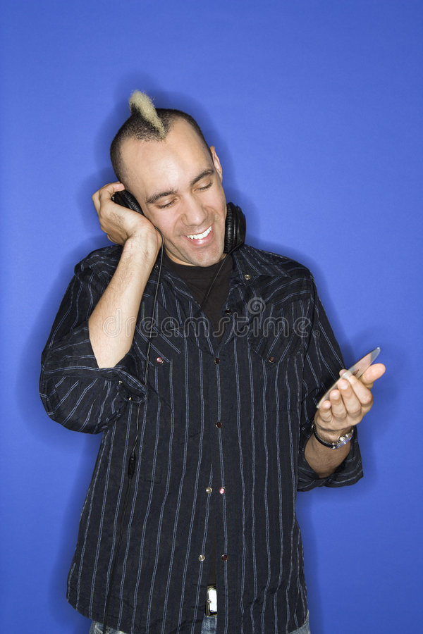 Caucasian man with mohawk listening to music. Caucasian man smiling with mohawk listening to headphones holding cd standing against blue background stock photo