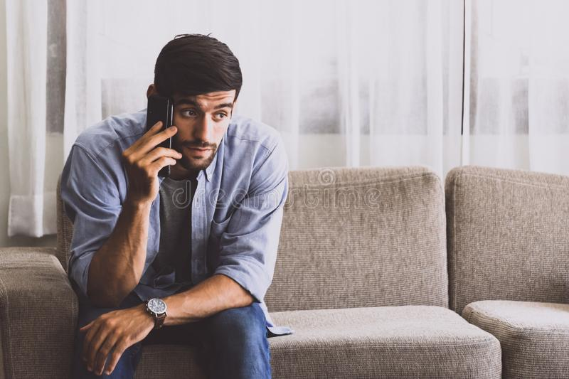 Caucasian man with mustache and beard talking with mobile phone in living room about serious problem royalty free stock photos