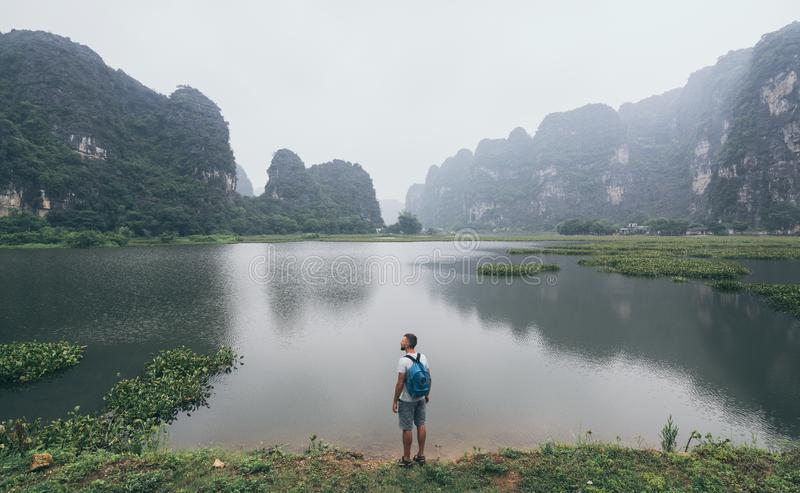 Caucasian man overlooking limestone mountains in Ninh Binh province, Vietnam. Cloudy day royalty free stock photo