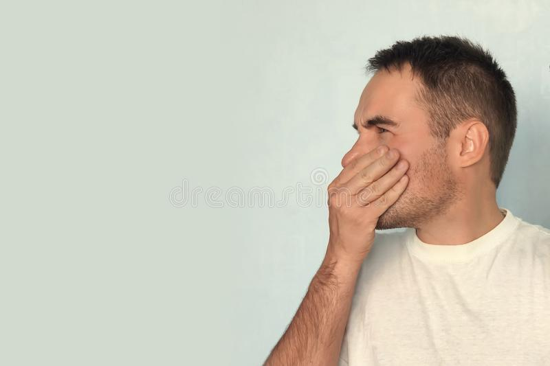 Caucasian man is pinching nose with fingers and looking with disgust because of bad smell on blue background. Negative human face stock images