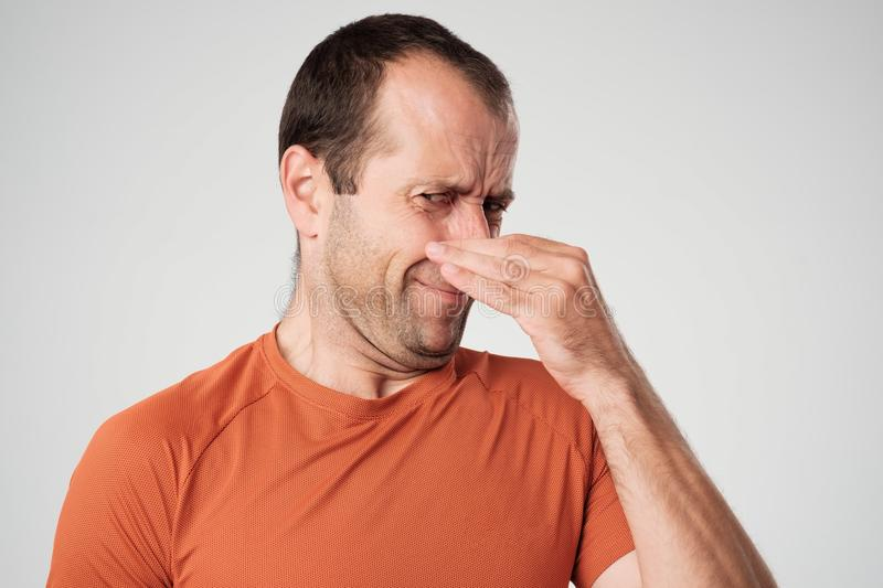 Caucasian man is pinching nose with fingers and looking with disgust because of bad smell isolated on white background royalty free stock photos