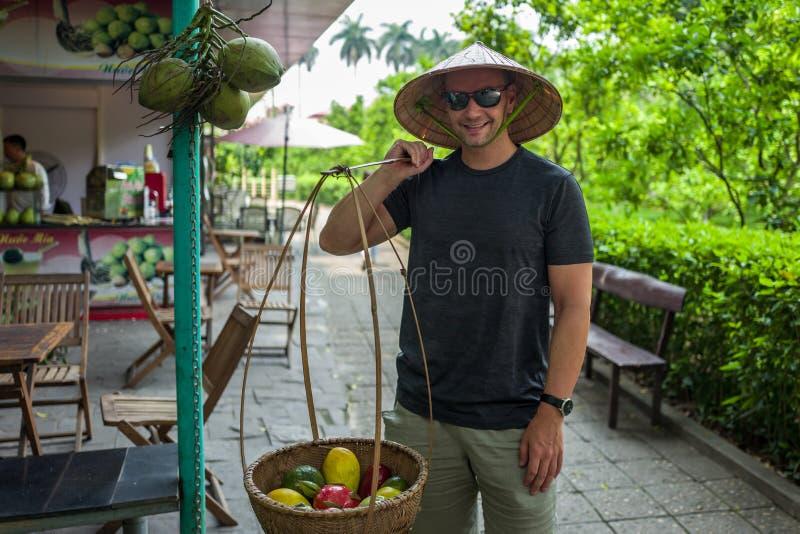 Caucasian man poses as street market seller in Hanoi, Vietnam.  stock photos