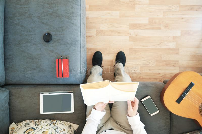 Caucasian man reading a book studying in the living room. Overhead shot from above and empty copy space stock image