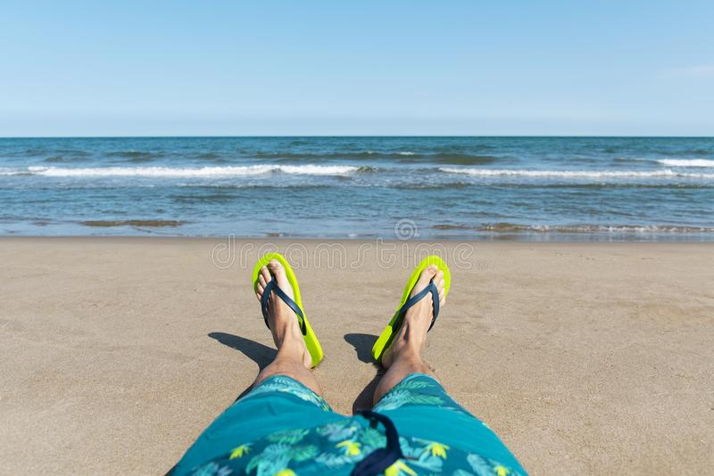 Caucasian man relaxing on the beach. Closeup of the legs of a young caucasian man relaxing on the beach, wearing a blue swimsuit and a pair of green flip-flops royalty free stock photos