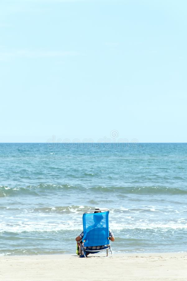 Caucasian man relaxing on the beach. A caucasian man, seen from behind, relaxing on the beach, sitting on a deck chair and wearing a pair of green flip-flops stock photo