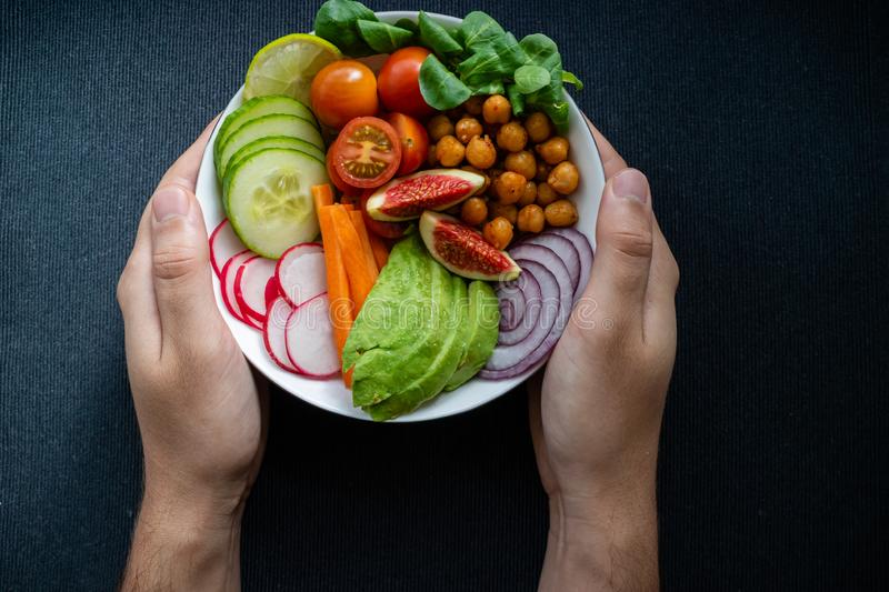 Caucasian man`s hands holding a Buddha bowl with vegan ingredients on dark background stock images