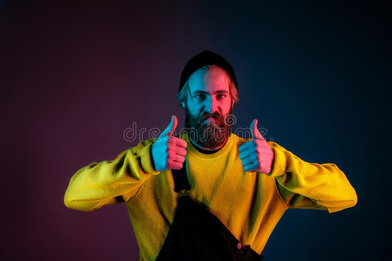 Caucasian man`s portrait isolated on gradient studio background in neon light royalty free stock photos